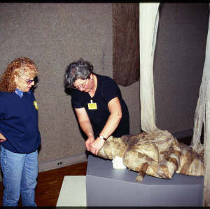 Color image of Judy Chicago, wearing a blue shirt and jeans, and another individual, wearing a black shirt, wrapping a mummy on a gray platform.