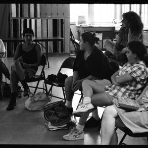 Black and white image of Judy Chicago and other individuals sitting in a circle. Judy Chicago sits on a table. The others sit on folder chairs. The wall at the back of the room is lined with lockers.