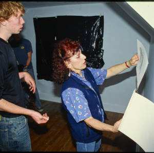 Judy Chicago and three students look at pencil sketches on white paper in a room with white walls, hardwood floors, and black plastic covering the window.