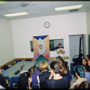 Color image of Judy Chicago and other indiduvals gathered in a semi-circle around a multi-colored artwork.