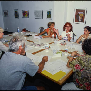 Color image of Judy Chicago and other individuals sitting around a white table trimmed in woodwork. On the table there are sketches, water bottles, and food. The room features a white wall lined with framed artwork.