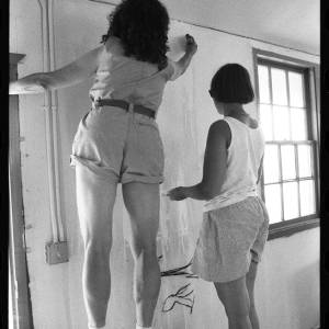 Black and white image of Judy Chicago and another woman, who both wear shorts, painting a wall.