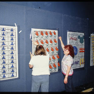 Color image of Judy Chicago and another indiduval hanging mulit-colored artworks on blue walls.