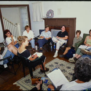 Color image of 10 people sitting in a circle in a room with white walls, dark wood work, hardwood floors, and a white floral aread rug.
