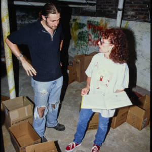 Color image of Judy Chicago in jeans, a white tee shirt, and red sneakers speaking with a student, who is wearing a blakc shirt and ripped jeans.