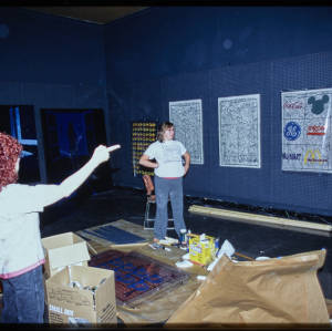 Color image of a woman and Judy Chicago surrounded by cardboard boxes, and pointing to artwork on a dark blue wall.