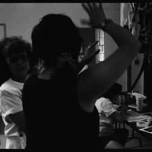 Black and white image of Judy Chicago facing another gesturing indiduval. Another individual in the backgroud works at a table.