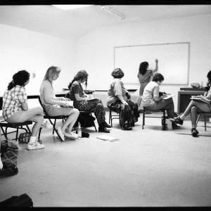 Black and white image of individuals sitting in a circle of folding chairs turn to face Judy Chicago writing on a white board.