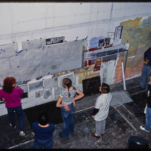 Color Image of Judy Chicago and other indivudals viewing architechtural drawings hung on a wall.