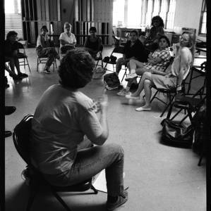 Black and white image of Judy Chicago and a group of individuals sitting in a circle on folding chairs facing an individual sitting in the center of the circle on a folding chair.