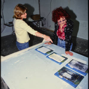 Color image of Judy Chicago and another individual in a yellow shirt pointing to small canvases on a white table.