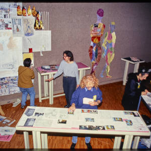 Color image of Judy Chicago and other individuals in a room with gray walls and hardwood floors. Some participants view and hang multi-colored art on the walls. Others view multi-colored art on tables.