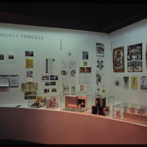Color image of white semi-circular exhibition installation with multi-color art work in glass boxes, and hung on the white walls. Clipboards are hung on the white walls.