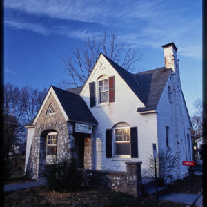 Color image of the At Home house. Features a white brick home with black shutters, black roof, and a stone facade.