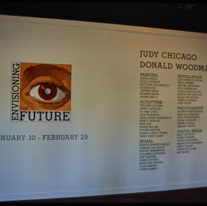 Color image of exhibition installation wall with black text and the Envisioning the Future logo, which features a brown eyeball.
