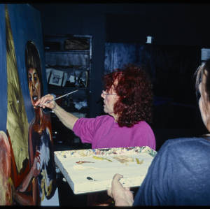Color image of Judy Chicago in pink shirt painting. Another indivudal, wearing a blue shirt, with their back to the camera holds a pallete of paint.