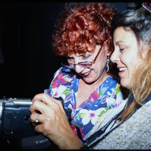 Color image of Judy Chicago wearing a multi-color floral shirt with another individual wearing a white sweater. Both are looking at a camcorder.