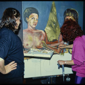 Color image of Judy Chicago in a pink shirt and another inidvidual in a blue shirt painiting a large canvas featuring a naked woman.