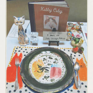 Color image of student artwork. Images focuses on a Dinner Party place setting. The place setting is mulit-colored, and features a ceramic cat.